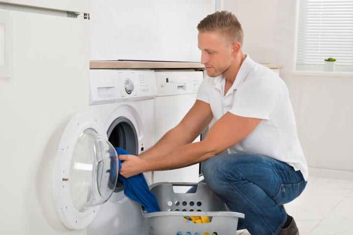 Man Loading Washing Machine With Clothes