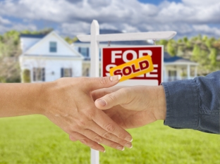 Man and Woman Shaking Hands in Front of a Beautiful New House an