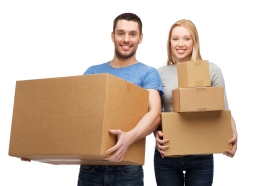 moving, home and family concept - smiling couple holding cardboa